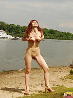 A sexy redhead naked at the nude beach.